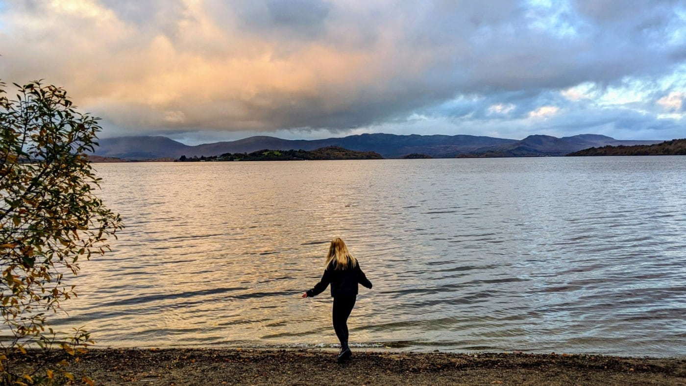 An IKEA store co-worker from the IKEA Glasgow store standing by the shore of Loch Lomond lake in Scotland with her arms spread out.