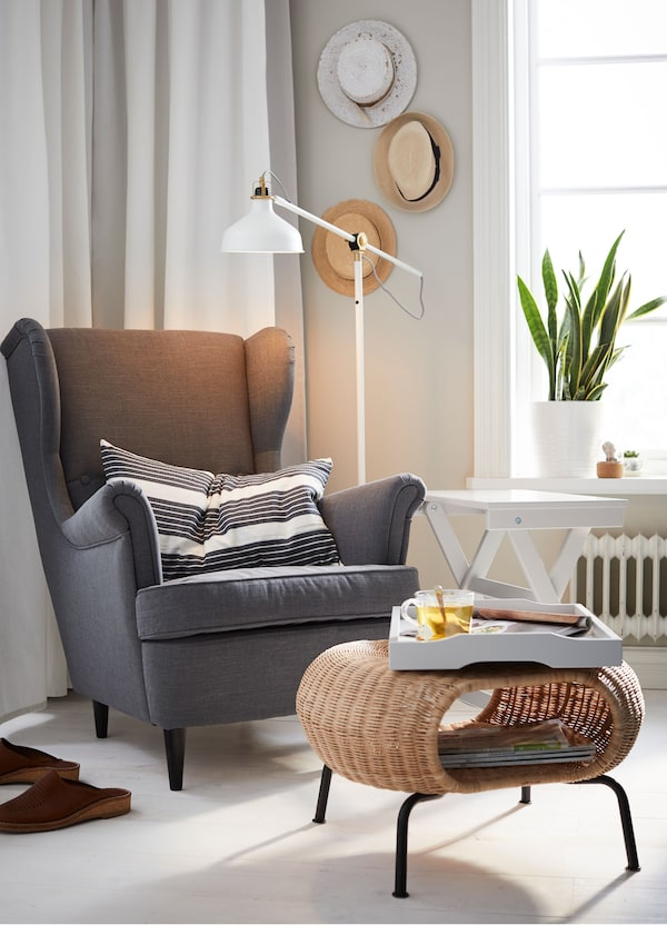 An IKEA STRANDMON dark grey wing chair in the corner of a living space, with a rattan coffee table and tray.