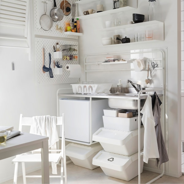 An IKEA SUNNERSTA mini-kitchen in white, with shelves on the wall.