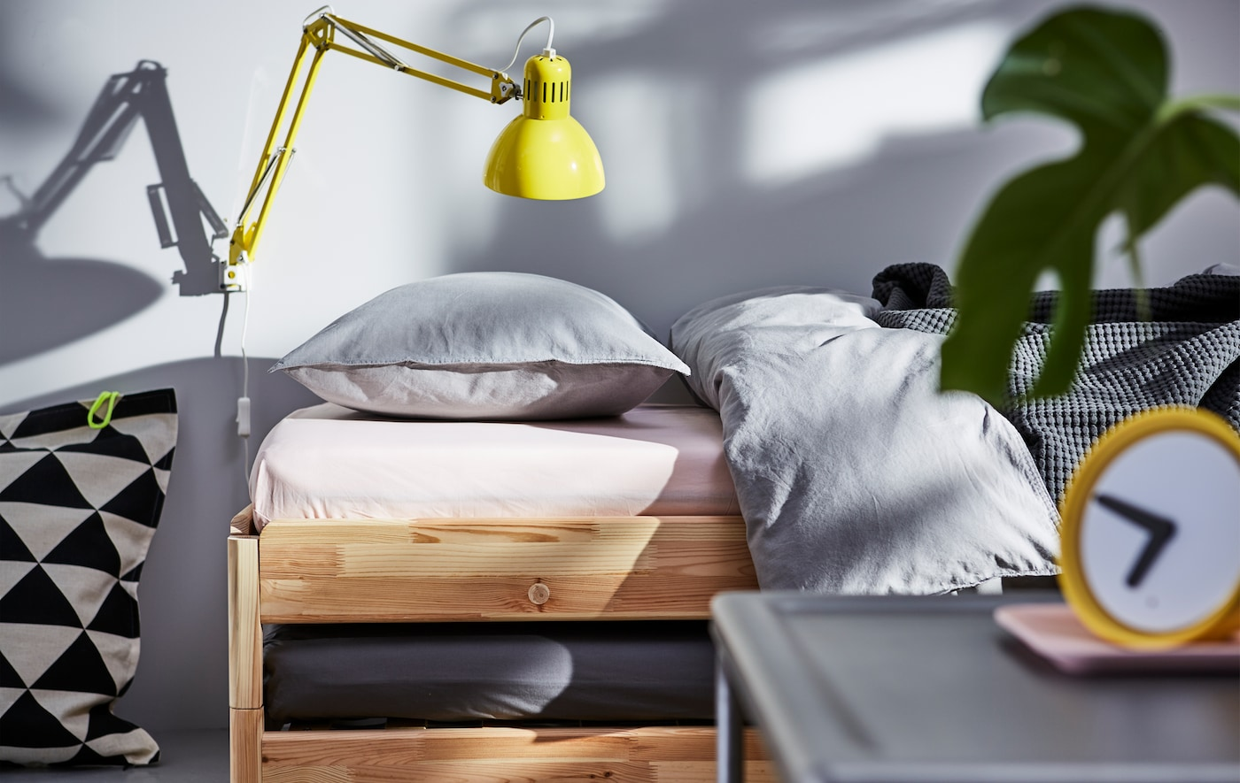 An IKEA UTÅKER bed with a yellow wall lamp over the pillow.