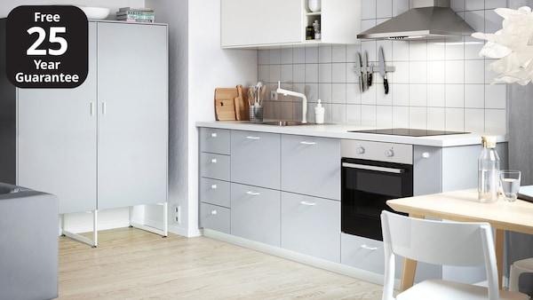 An IKEA VEDDINGE grey kitchen with light grey worktop and white door knobs.