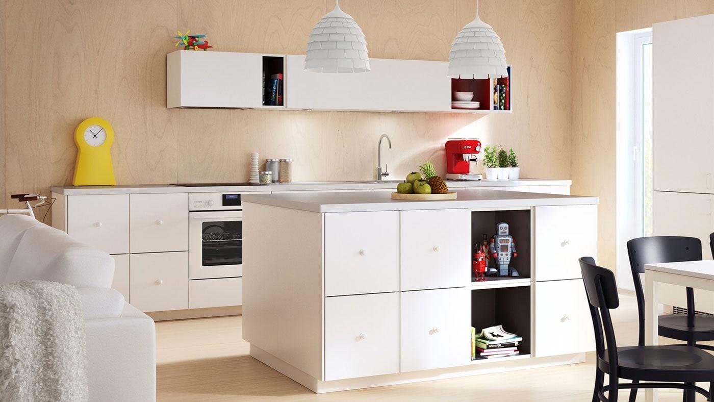 An IKEA VEDDINGE white kitchen with light grey worktop and white door knobs.