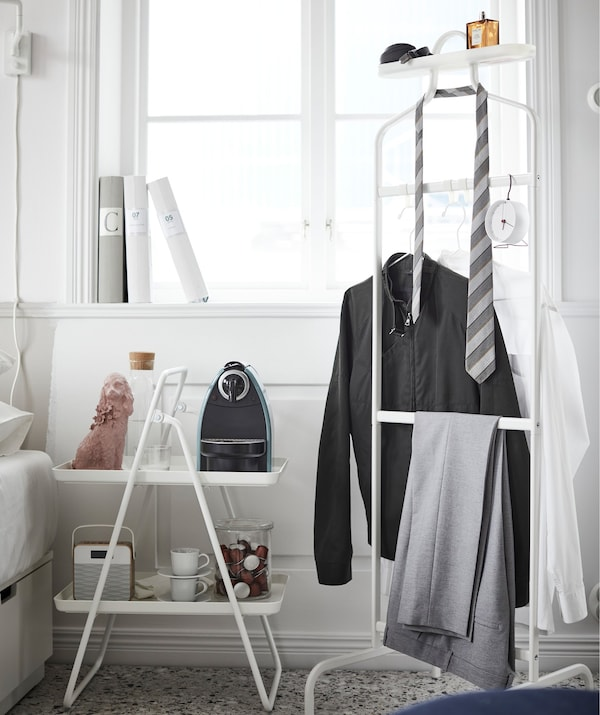 An IKEA VIGGJA tray stand acting as a coffee station next to a bed, with a rack holding hanging clothes beside it.