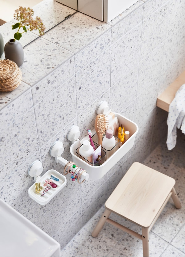 An IKEA VILTO birch step stool and white TISKEN suction cup soap dishes and hooks on a grey and white tiled wall.