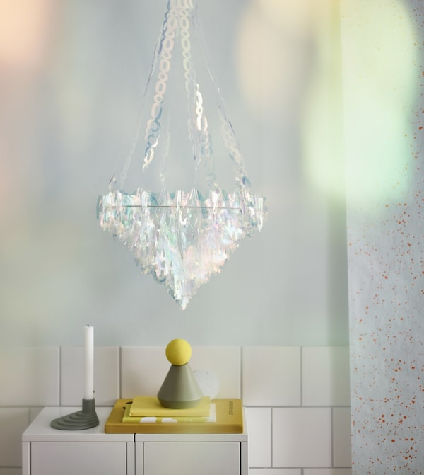 An IKEA VINTER 2017 hanging chandelier made of plastic, iridescent pieces that look like crystals glows in a room.
