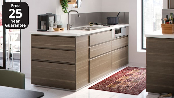 An IKEA VOXTORP kitchen in walnut effect with a white worktop.