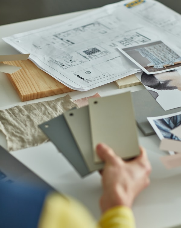 An IKEA worker showing differente colours to choose for an interior design