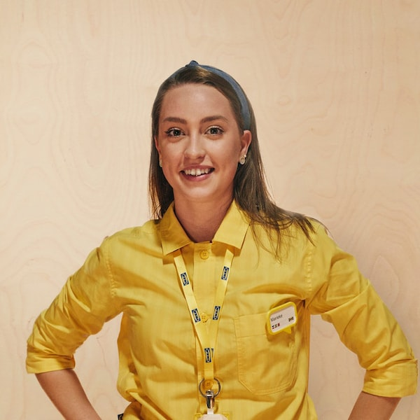 An IKEA worker smiling with her yellow uniform
