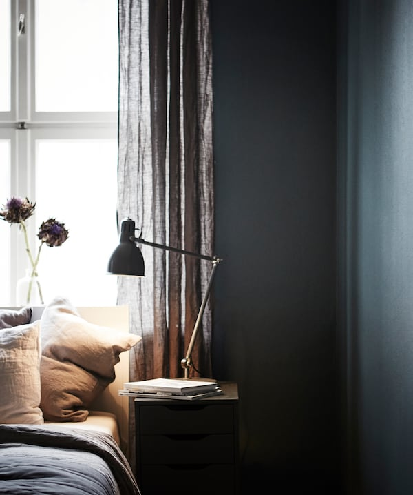 An image of a bed and bedside table in front of a window, surrounded by a dark wall.