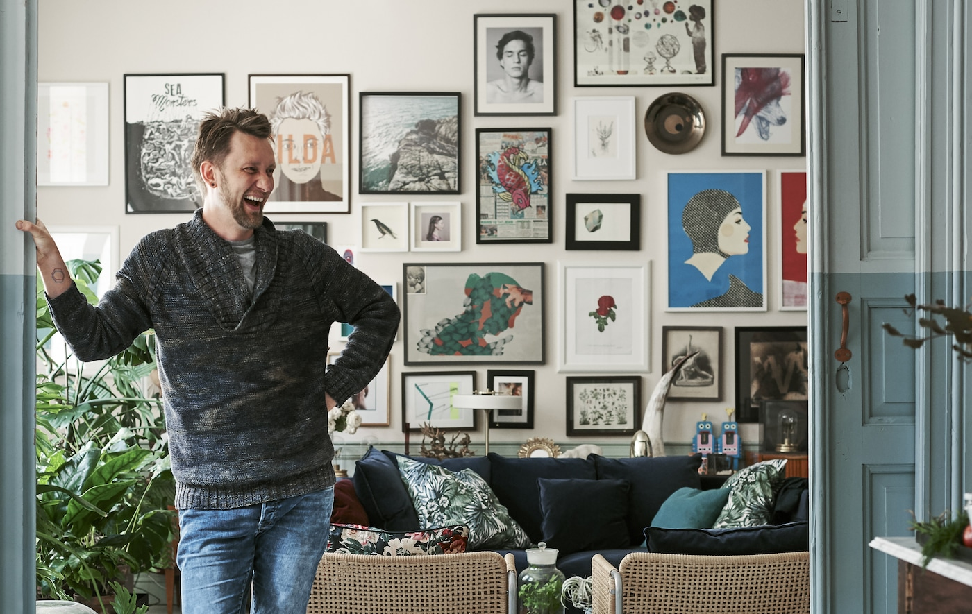 An image of a man standing in his lounge in front of a wall full of pictures.