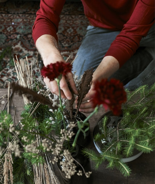 An image of Łukasz arranging flowers and sprigs in a vase.
