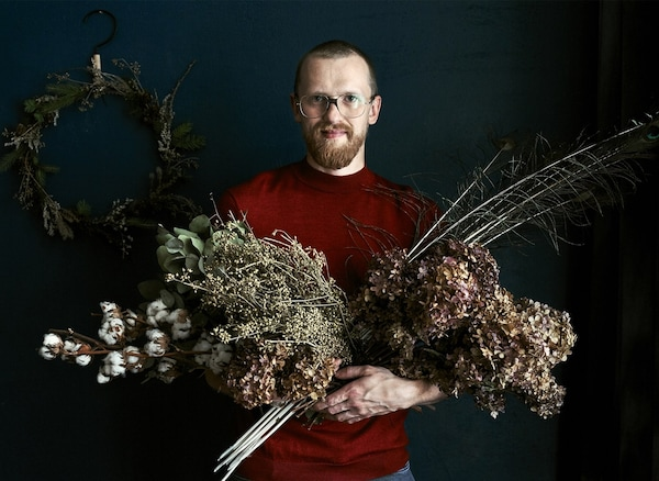 An image of Łukasz standing in front of a wreath holding armfuls of dried foliage.