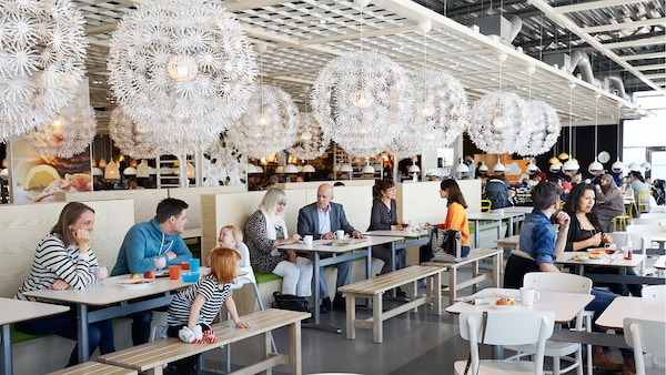 An image showing the seating area of an IKEA restaurant with people seated enjoying their meal.