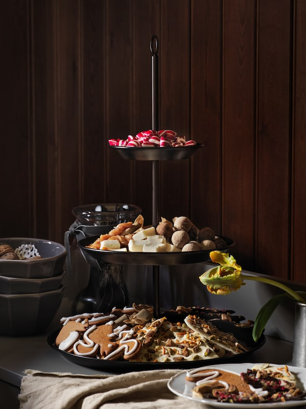 An INBRINGANDE serving stand on a sideboard is piled high with sweets and snacks ready for the party to come.