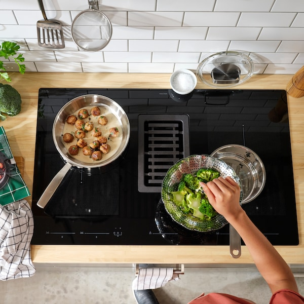 An induction hob with integrated extractor. Broccoli and meatballs are cooked here, and a person reaches in with one hand.