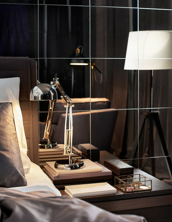 An industrial style work lamp sits on a bedside table in front of a mirrored wall.