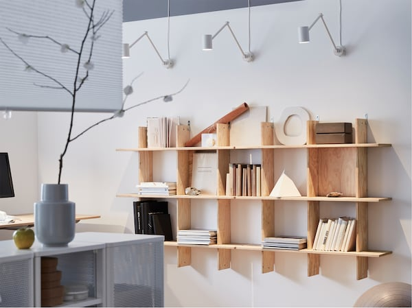 An INDUSTRIELL shelving unit illuminated by IKEA NYMÅNE white wall lamps, with adjustable arms.