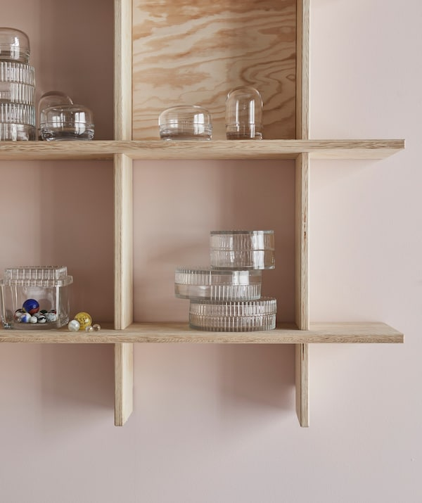 An INDUSTRIELL shelving unit with a few glass containers and marbles on display.