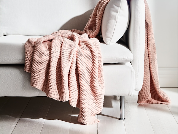 An INGABRITTA pale pink throw made from knitted cotton is draped over the end of a sofa in a room with a wooden floor.