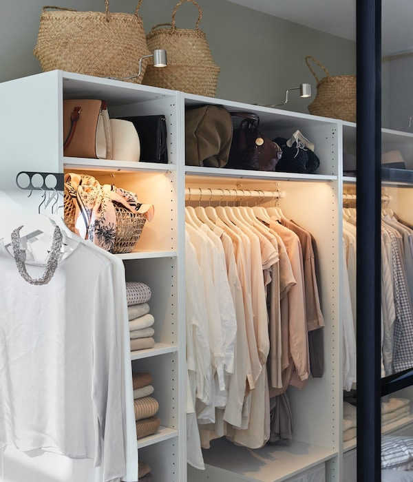 An inside view of a wardrobe system with illuminated clothing rail and several compartments.