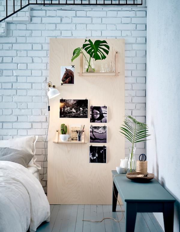 An inspiration board made of plywood leaning against a white brick wall in the bedroom.