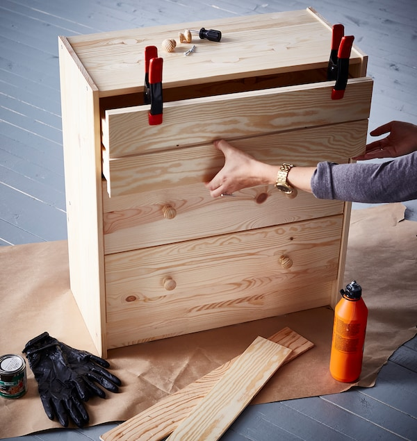 An interior designer clamps the top drawer front of an IKEA RAST 3 drawer chest that she's hacking for an upcycle.