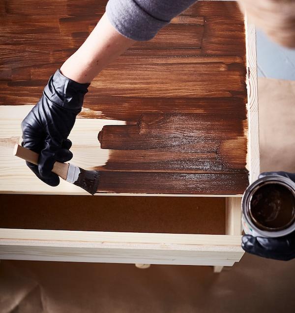 An interior designer wears black latex gloves while staining an IKEA RAST 3 drawer chest in dark brown.