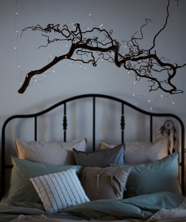 An intricately twisting, leafless tree branch adorned with VISSVASS lighting chain and hung over a cosily made bed.