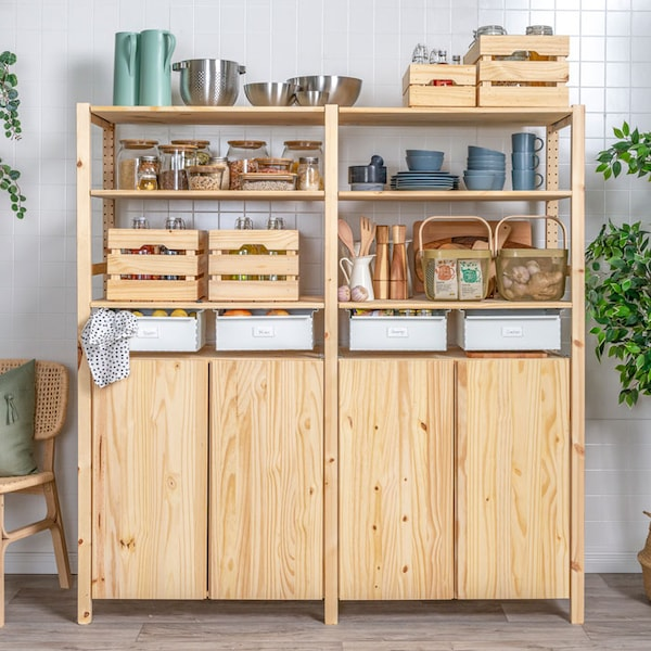 An IVAR pantry unit in a kitchen, holding various jars, cookware, storage baskets, and containers.