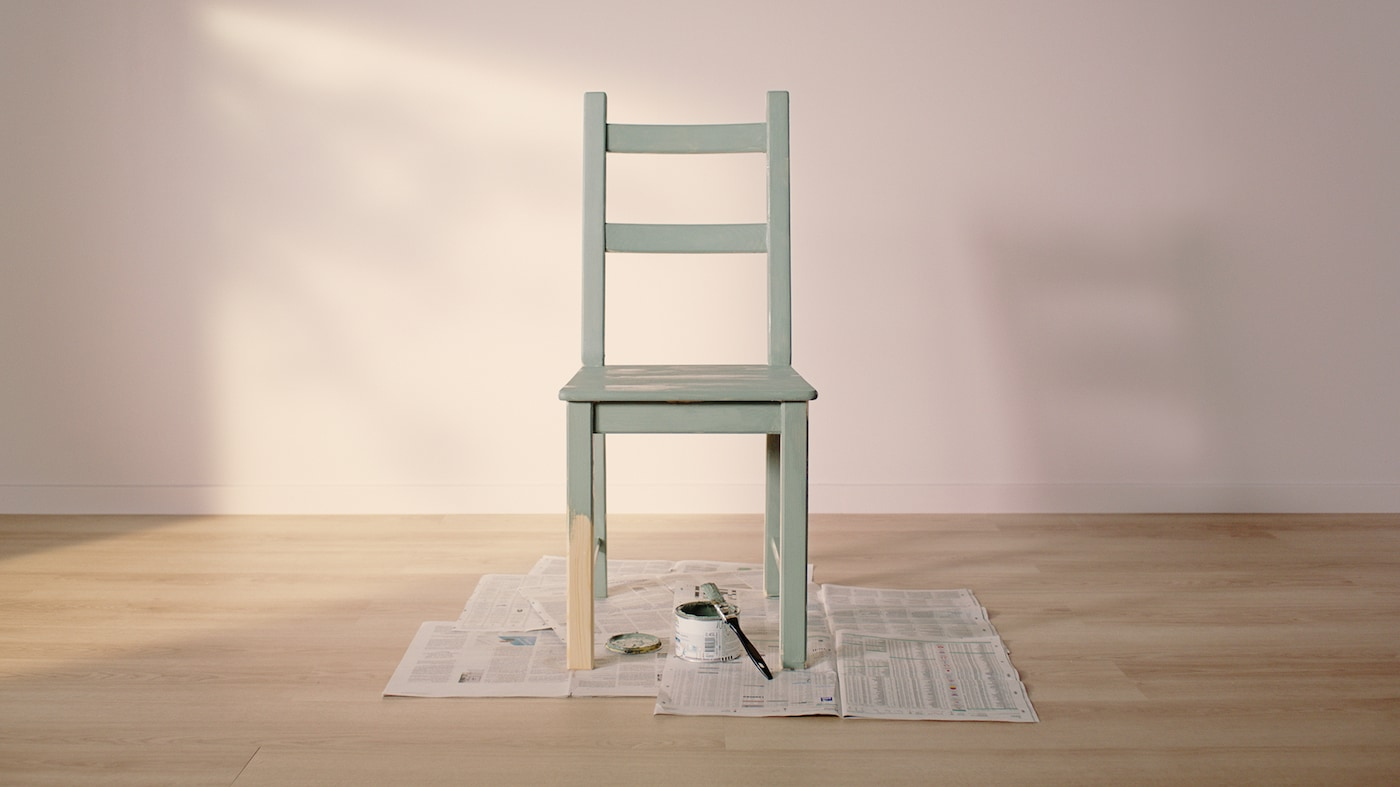 An IVAR pine chair, painted green apart from half of one leg, stands on newspaper with a tin of paint and a paintbrush.