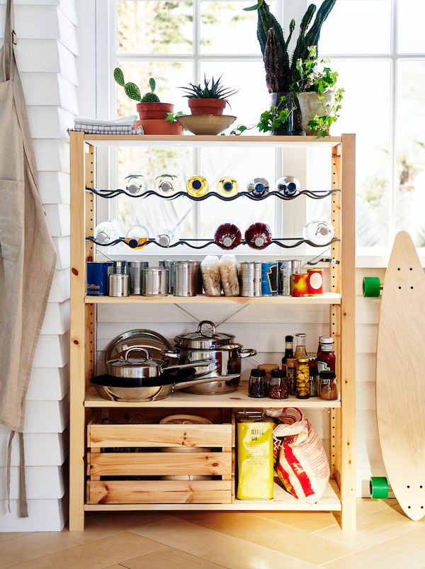 An IVAR unit stands by a window, organised as a small pantry with pots, dry goods, canned food, and bottles on racks.