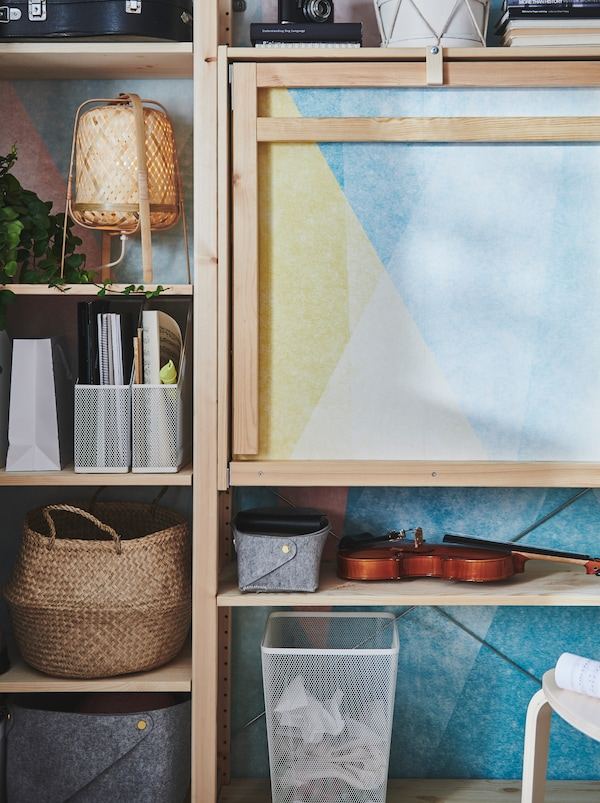 An IVAR wooden storage unit with a foldable table in unpainted wood, with items in metal, rattan and felt on the shelves.