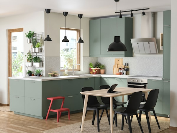 An L-shaped IKEA kitchen with green BODARP door and drawer fronts.