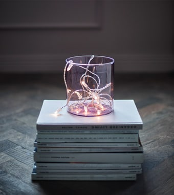 An LED lighting chain in a clear vase sitting on a stack of magazines