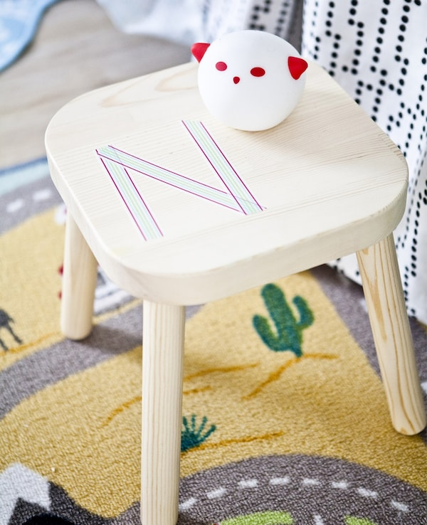 """An """"N"""" made with washi tape personalises this wood stool turned bedside table in a child's bedroom."""