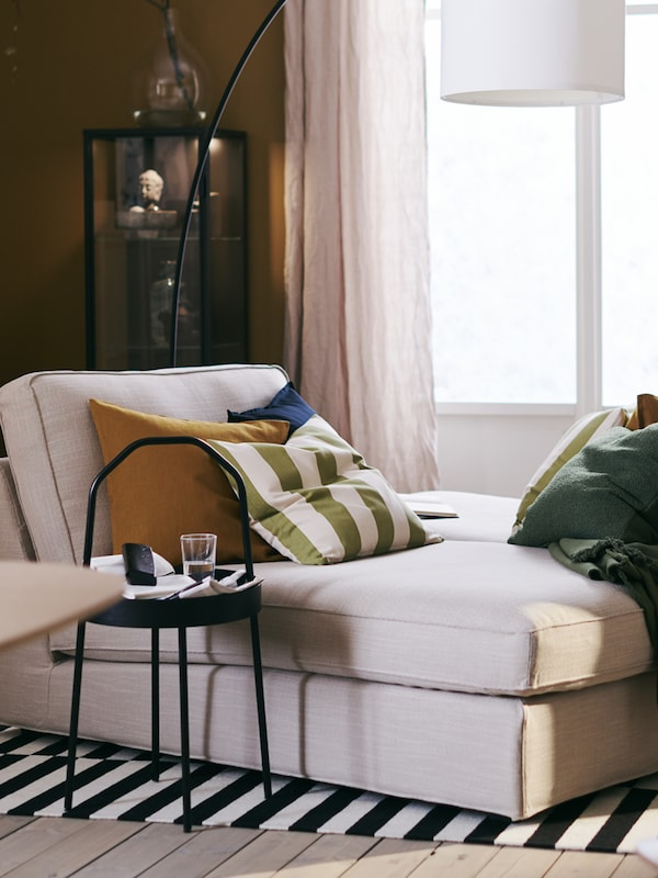 An ochre-toned living room with two beige KIVIK chaise longues next to each other by a window on a black and white rug.