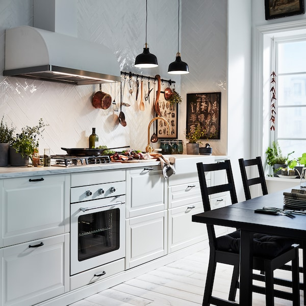 An off-white BODBYN kitchen is illuminated by two black pendant lamps. A black table and two black chairs stand beside.