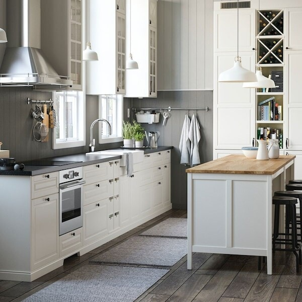 An off-white IKEA BODBYN kitchen with dark worktops and freestanding island with stools.