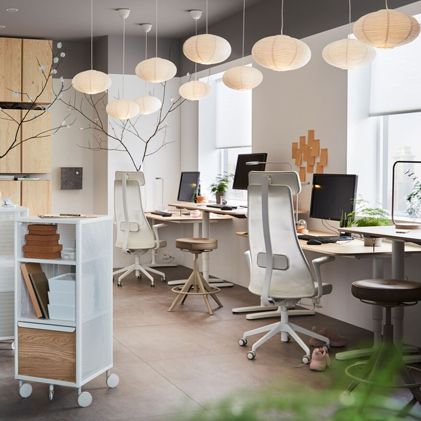 An office furnished with ergonomic IKEA JÄRVFJÄLLET swivel chairs, IVAR pine storage cabinets and BEKANT oak veneer work desks.