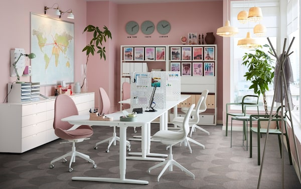 An office space with pink walls and white BEKANT sit-stand work desks, with HATTEFJÄLL swivel chairs.