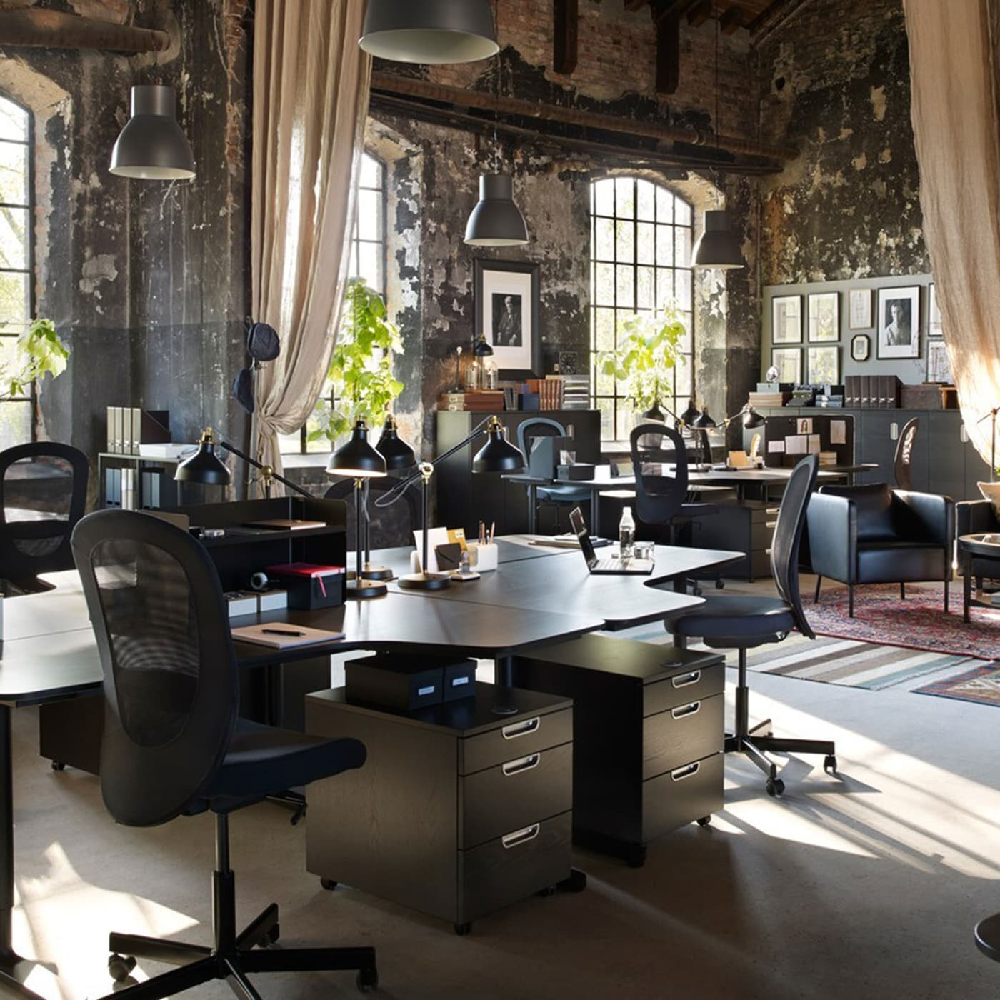 An office space with vintage room decor and modern IKEA BEKANT black work desks and FLINTAN black high-back swivel chairs.