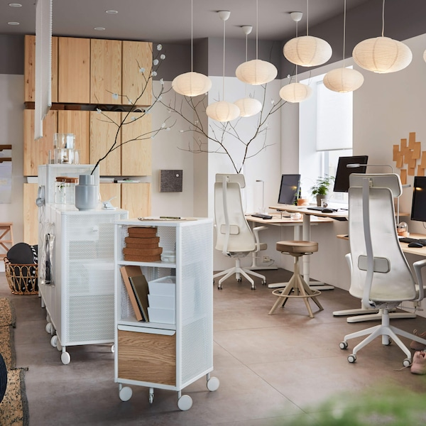 An office which white chairs, pendant lamps, and a rolling cart.