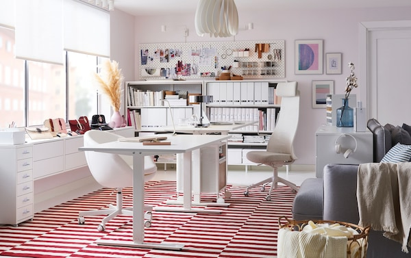An office with white chairs, a white sit/stand desk, and a red and white striped rug