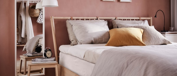 An old pink bedroom with a wooden bed and a white mirror