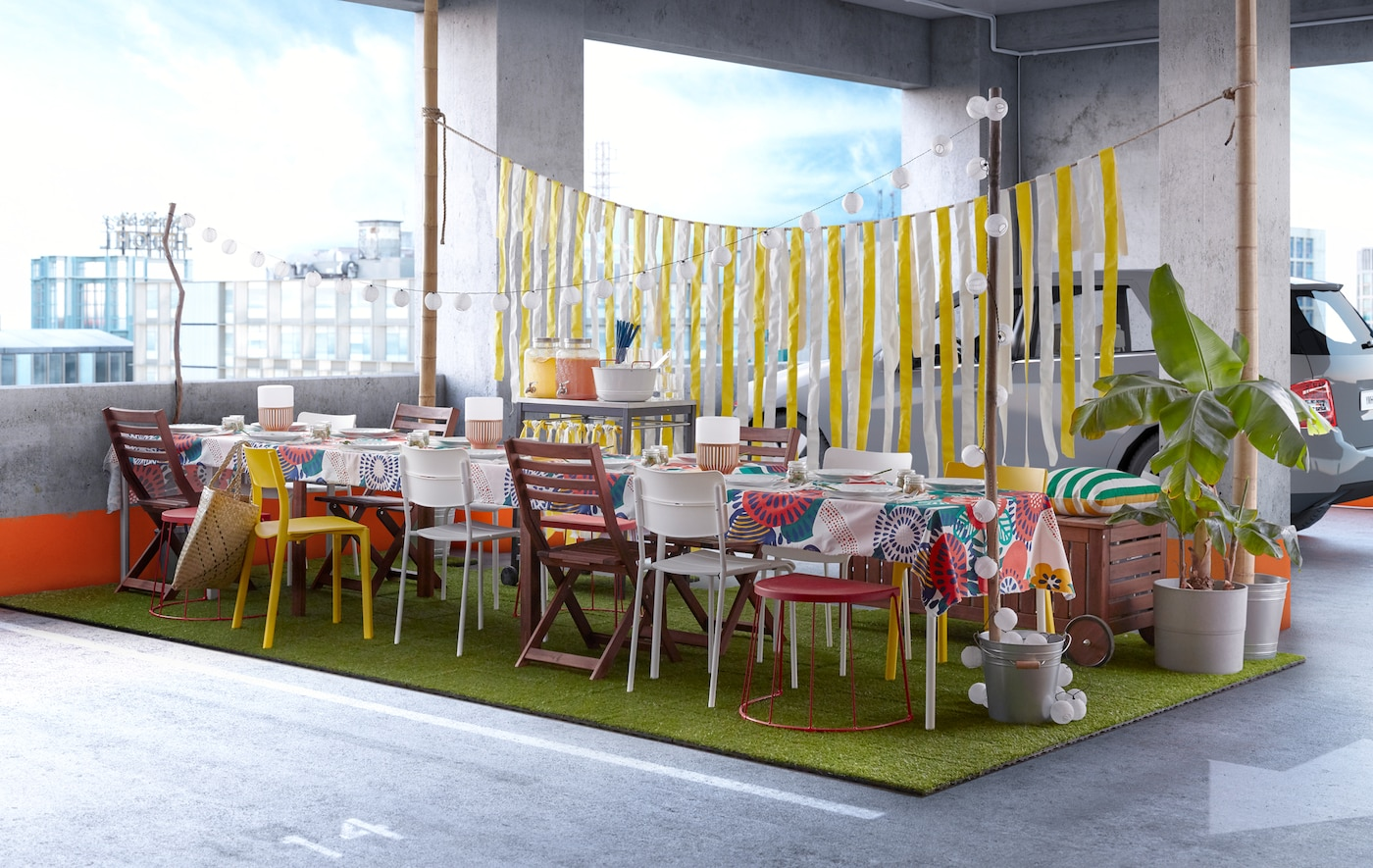 An open air dinner party scene with tables and seating in a urban car park setting.