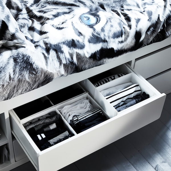An open and organized drawer with clothes inside SLÄKT white bed frame with storage.