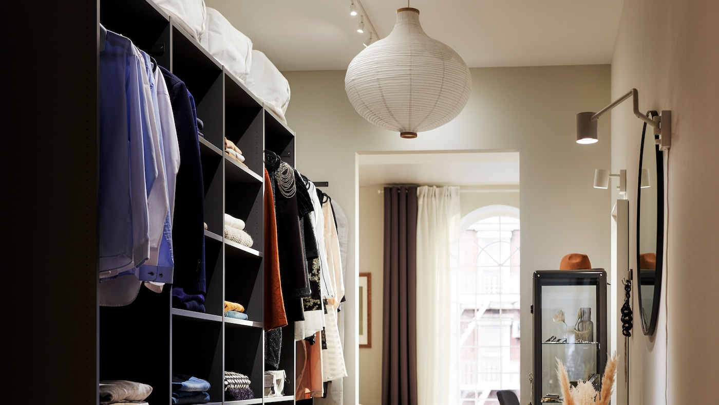 An open AURDAL wardrobe with clothes folded on shelves and hanging on rails stands opposite a wall with mirrors and lamps.
