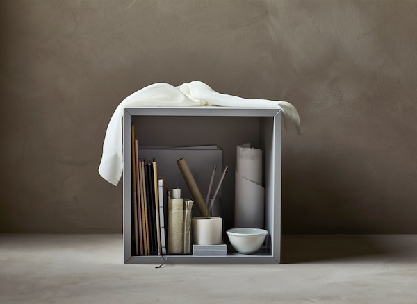 An open cabinet filled with art supplies such as paint brushes.