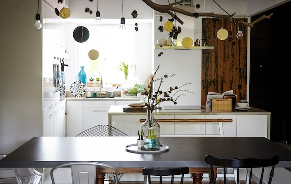 An open dining and kitchen space, with a black dining table, and light bulbs and paper decorations hanging from the ceiling.