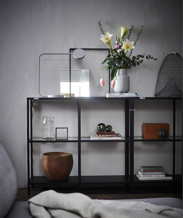 An open display unit against a grey wall, with a flower arrangement, books and decorative items.